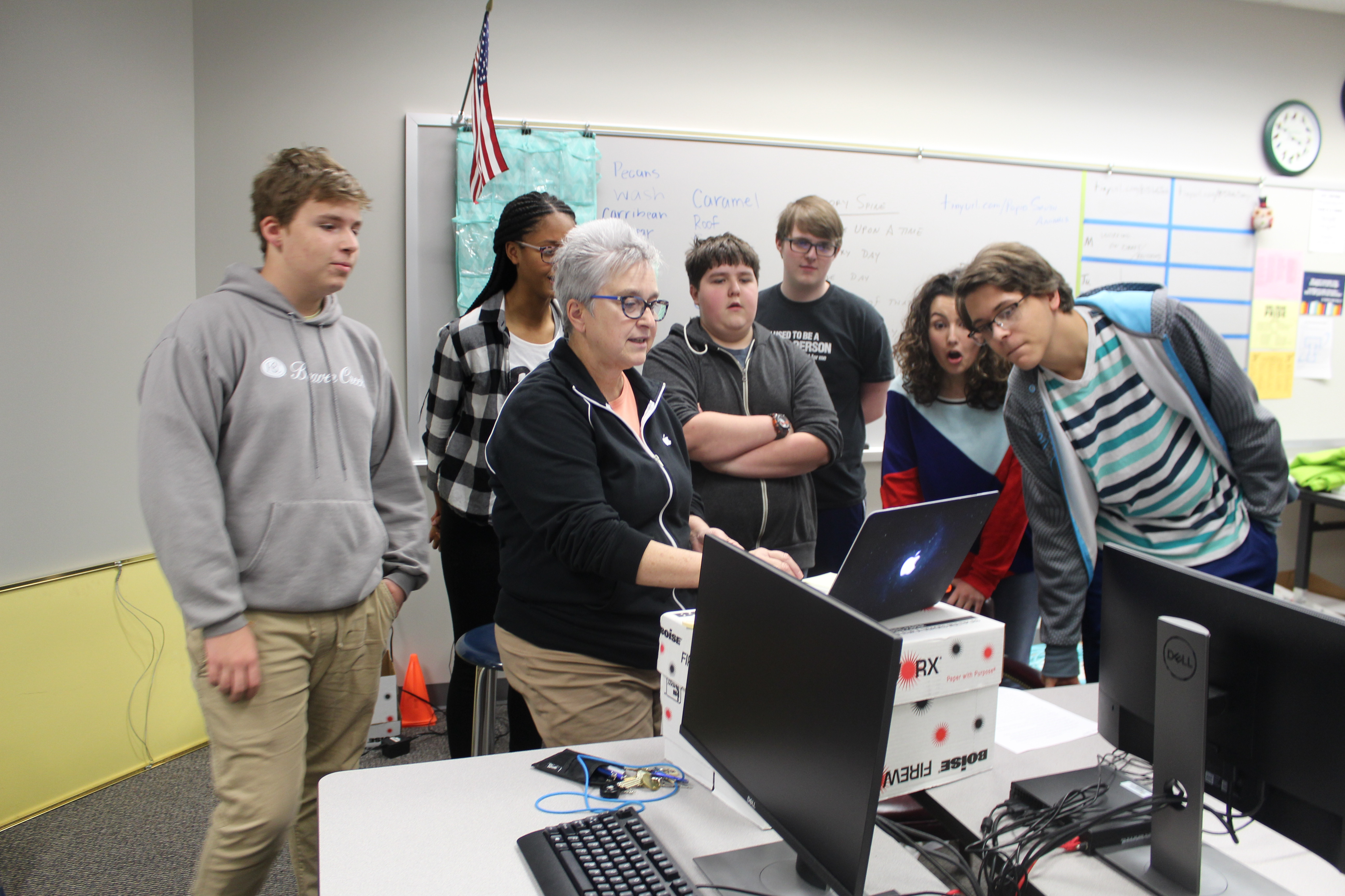 Technology club stands around a computer