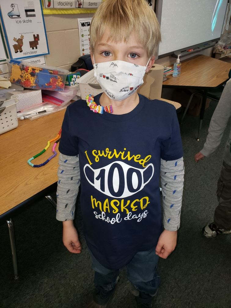 "Student poses for a picture with a shirt that says ""I survived 100 masked school days"""