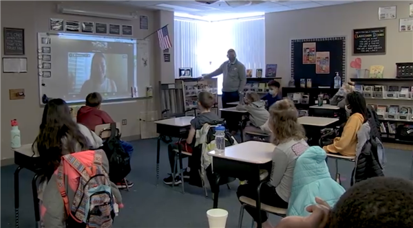 Students sitting in their desks in the classroom virtually meeting with an author over Zoom.