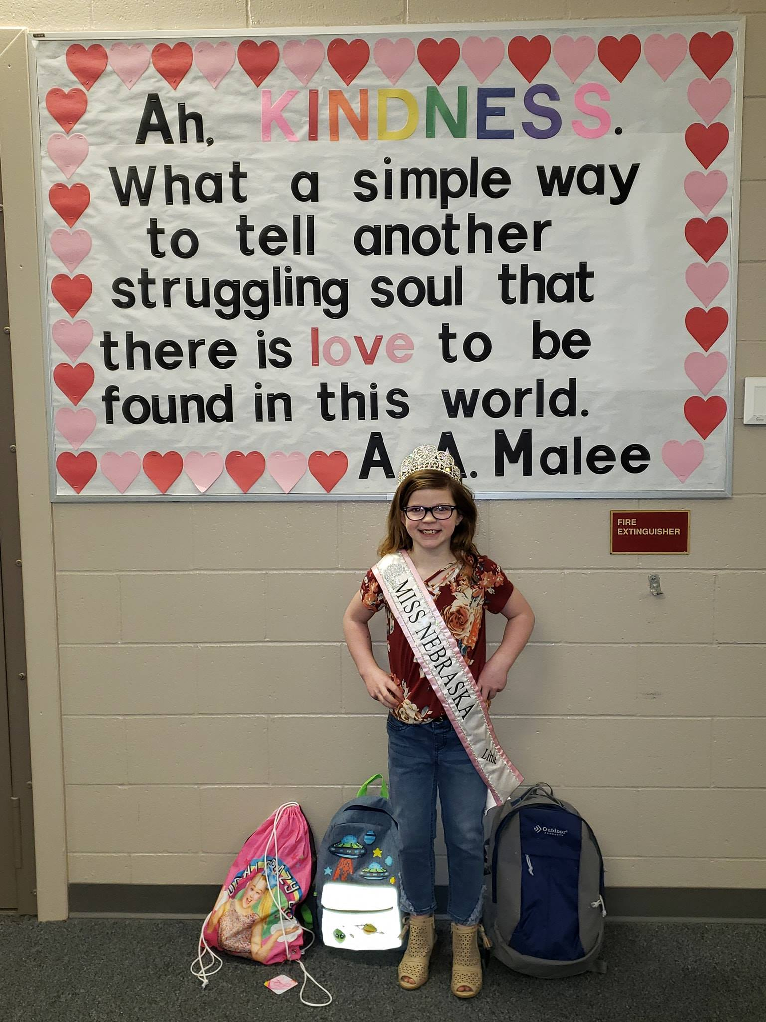 Little Miss Nebraska poses with school supply donation