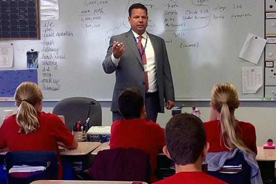 Kevyn Sopinski, a financial adviser with Waddell & Reed, visits with sixth-graders at Bell.