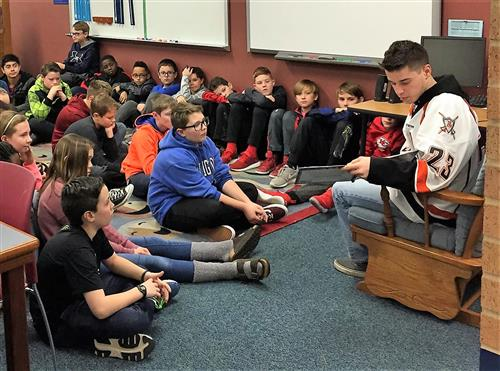 Chase Brand of the Omaha Lancers reads to a Patriot Elementary class