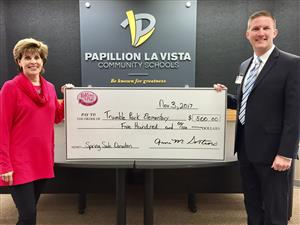 President of ReRuns R Fun Anna Sortino hols a check to be donated to PLCS with Dr. Andrew Rikli.