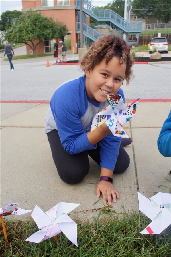 A student holds up her pinwheel in front of G Stanley Hall elementary she created for #BeKind.