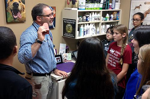 Dr. Michael Siggers shows a group of middle school HAL students around his practice.