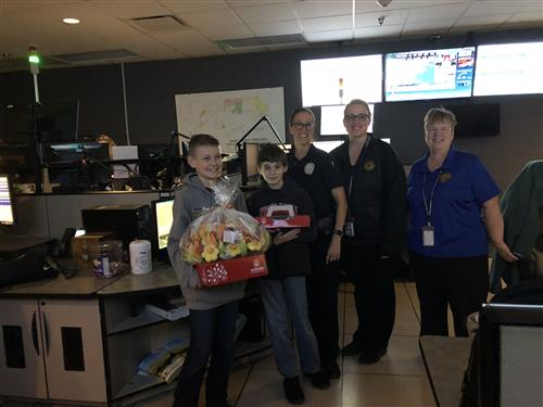 7th grade students, with LVPD LVMS SRO Officer Jamie Brown deliver treats to Sarpy 911 Center.