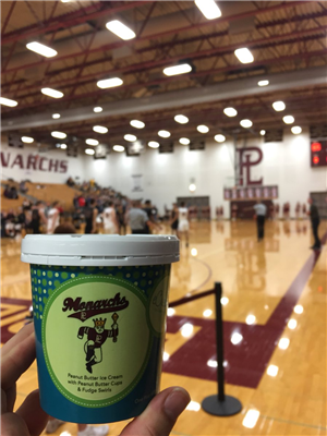 Student holds up pint of Monarch ice cream from eCreamery inside the gym at Papillion-La Vista H.S.