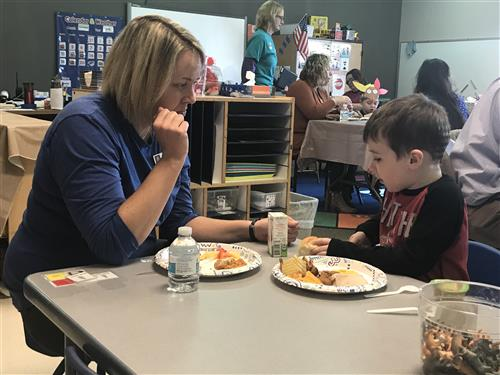 Katey Gigstead, PLCS Speech Pathologist & a preschool student enjoy potluck feast for Thanksgiving.