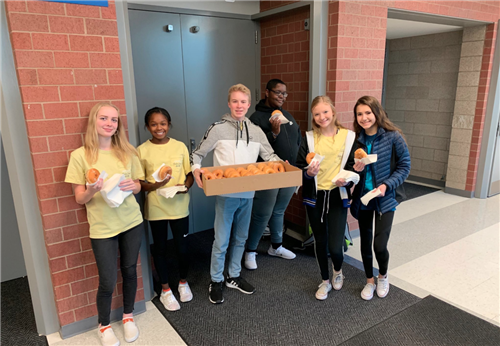 PLSHS student council members pose for a photo as they hand out donuts on World Kindness Day.