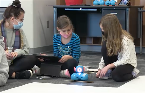 Three students working together using a Dash robot to practice measurement skills.