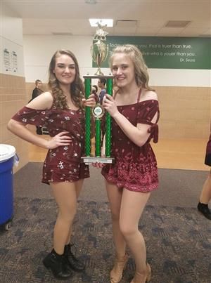 Two members of Heart and Soul hold up the team's 1st runner up trophy.