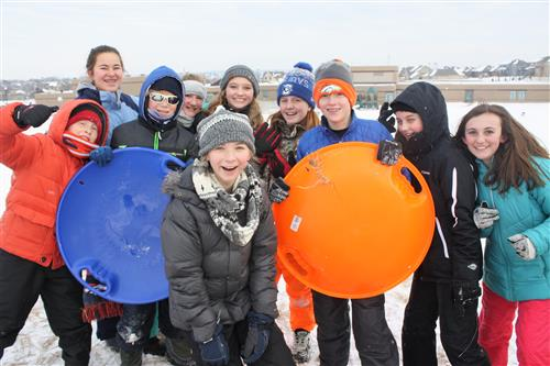 Bell students take to the hill outback of school for a lesson in sledding. A group stands for a pic