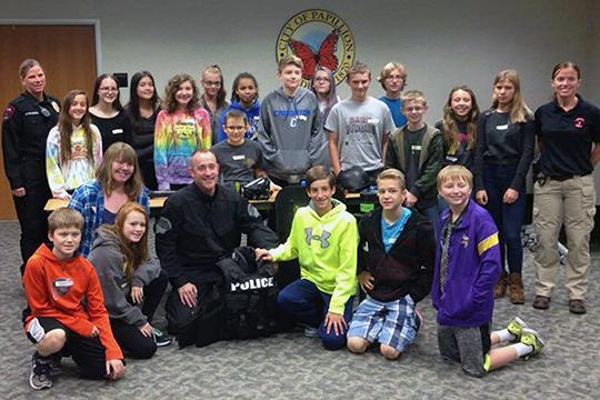 Students pose for a group photo with Papillion Police Sgt. Preston Maas with during a seminar.