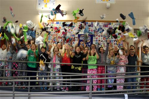 Hickory Hill student council members throw socks into the air after collecting nearly 1,400 pairs.