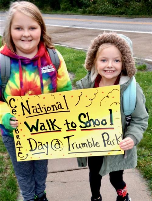 Harper and Olivia Howick from Trumble Park hold up a sign during Walk to School Day on the sidewalk