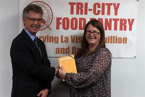 Doug Lewis presents Connie Shattuck, Tri-City Food Pantry director, with a check for $2,125.