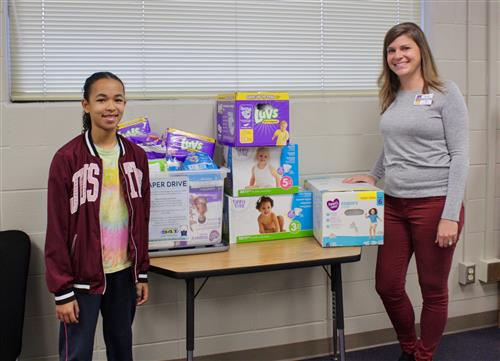 6th grade teacher Amy Vecchio and her student Lext Hatcher proudly display their 800 diapers.