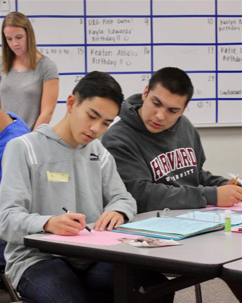 Two male high school students work together on a worksheet in the classroom.