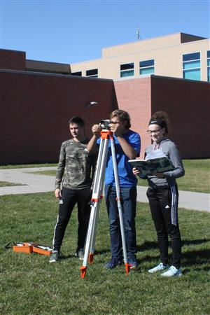 Three STEM academy students are learning how to use tools to do surveying.