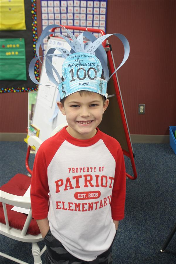 student showing his 100th day hat
